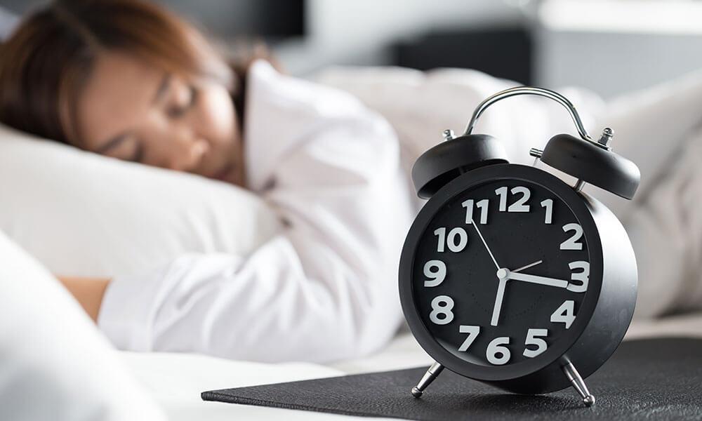 Alarm Clock Next to Sleeping Woman